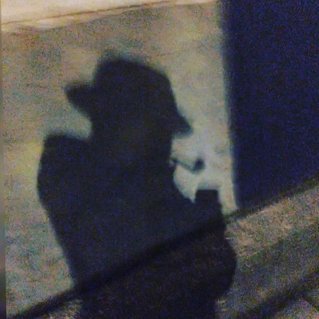 Shadow of man with hat and pipe